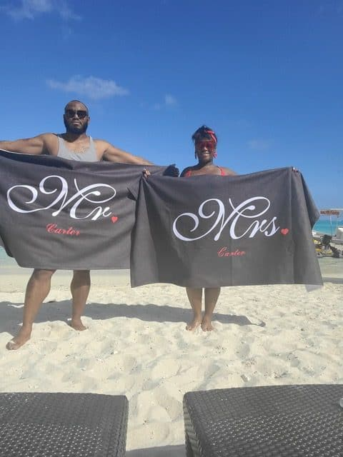 happy black couple at the beach wearing towel