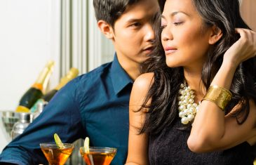 Asian man and woman in flirting intimately at bar drinking cockt