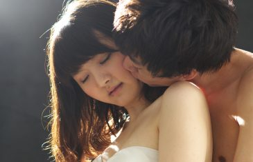 young Asian couple kissing, people isolated on black
