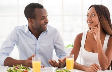 Beautiful young African couple sitting together at the breakfast table and talking