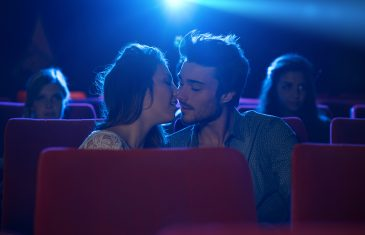 Young romantic loving couple kissing at the cinema relationships and lifestyle concept