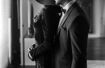 Sexy rich man in tuxedo with whip and lover indoor black and white bdsm