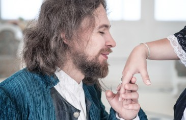Handsome man in medieval dress kissing hand of beautiful woman