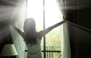 back of girl opening curtains in a bedroom