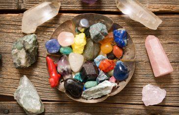 Multiple semi precious gemstones on wooden board fluorite, quartz, smoky quartz, rose quartz and others