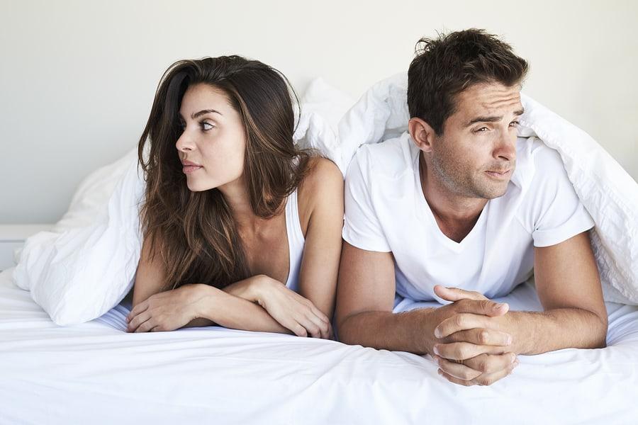 Awkward couple lying in bed looking away