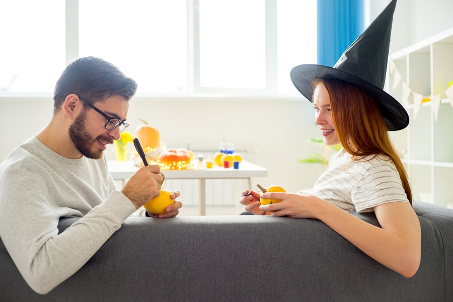 Happy couple playing with halloween pumpkins at home