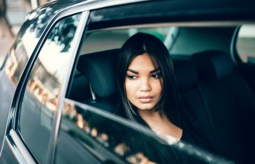 Beautiful young woman sitting on back seat of a car and looking outside the window