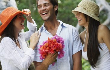 Man holding flowers between two women