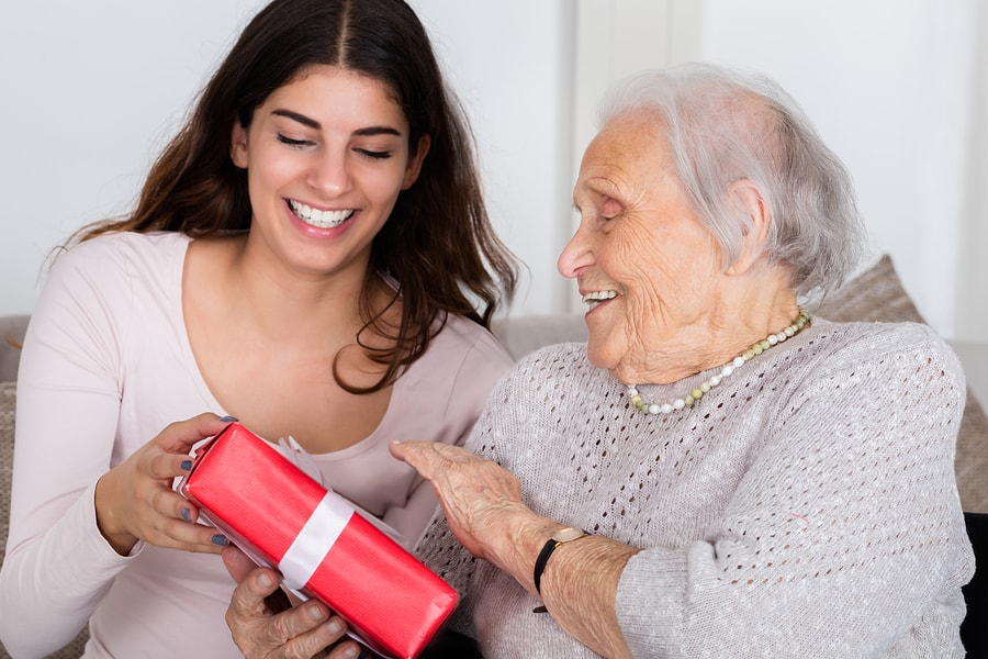 Happy Grandmother receiving Gift from Her Granddaughter