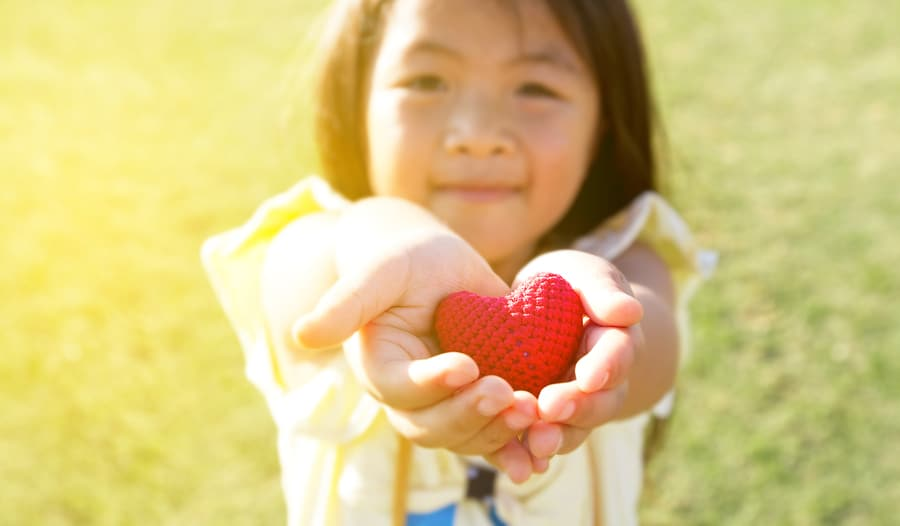 child holding red heart in her hands