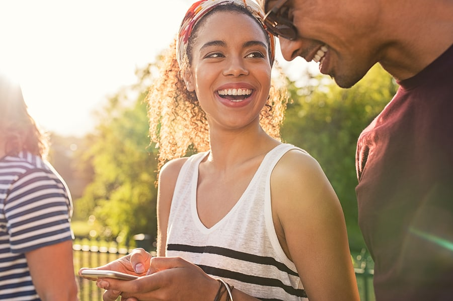 Cheerful african woman holding smartphone and looking her boyfri