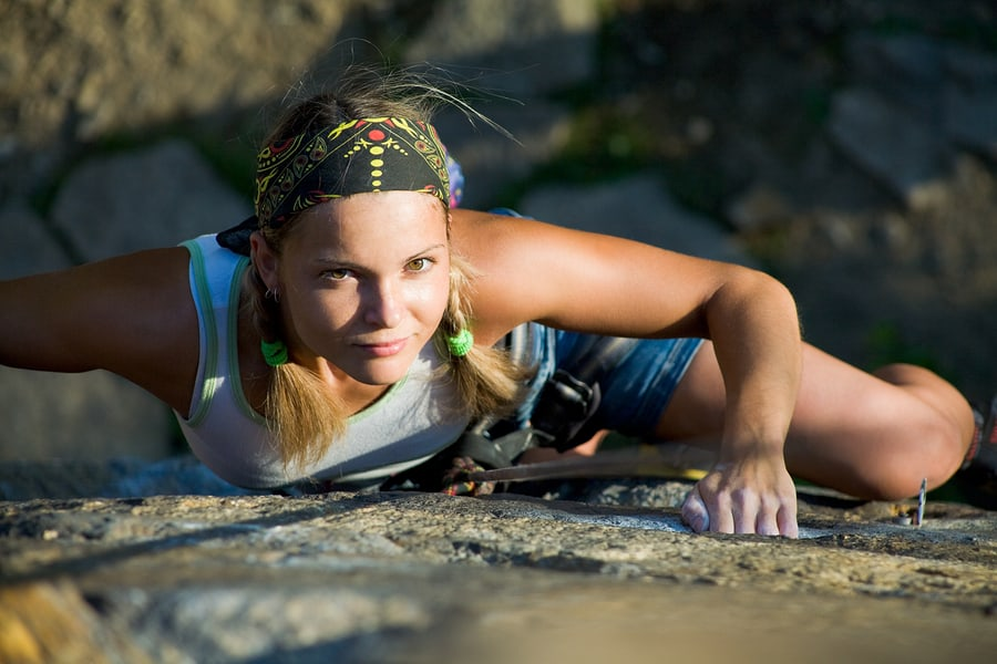 blonde lady climbing on the rock