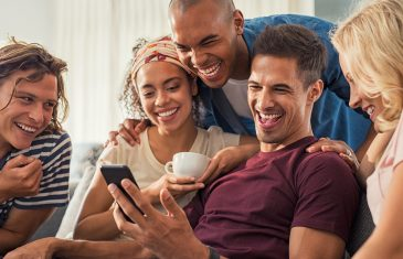 Joyful man showing video on his mobile phone with friends. Group