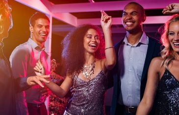 Cheerful girl dancing at night party with her friends