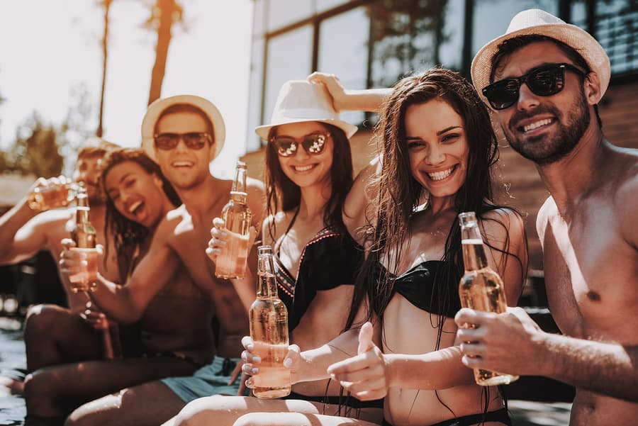 Young Friends With Alcoholic Drinks At Poolside
