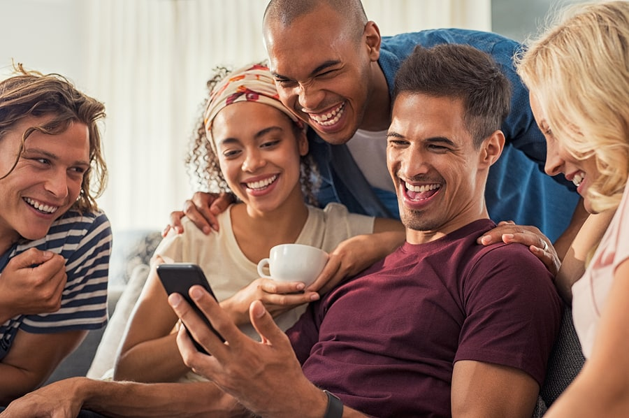 Joyful man showing video on his mobile phone with friends