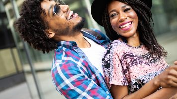 Happy Young Black Couple Hugging And Laughing Outdoors.