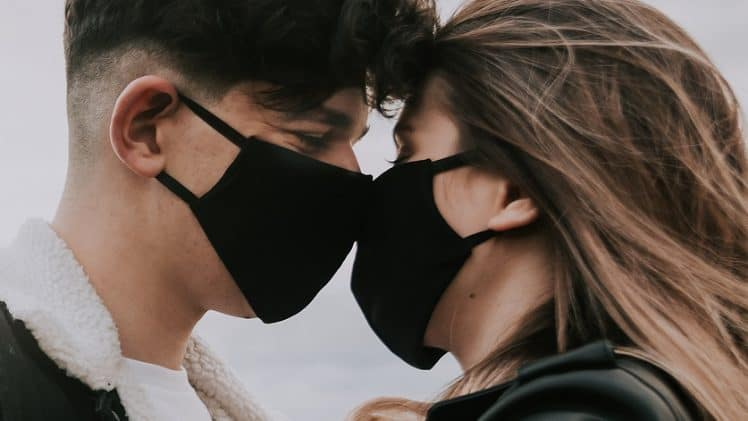 A Couple In Black Masks And Gloves Hold Hands